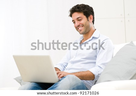 Happy smiling young man watching and working on computer laptop at home - stock photo