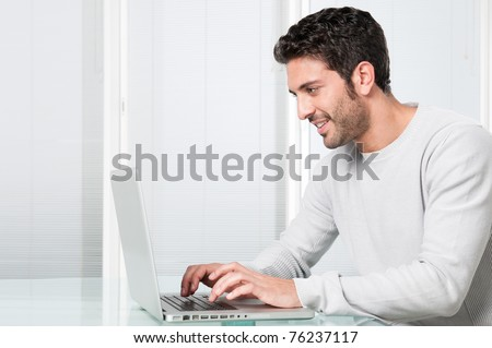 Happy smiling young man working and typing on laptop at home