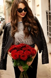 Happy smiling young pretty beautiful woman wearing stylish skirt, t-shirt, leather jacket and sunglasses and holding red roses bouquet