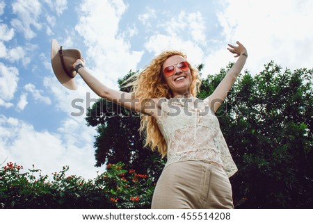 happy smiling young pretty woman with hat in her hand in sunglasses shows freedom and good mood on blue sky and green trees background.
