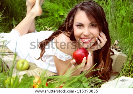 Happy Smiling Young Woman Eating  Apple in the Orchard. Basket of Apples.