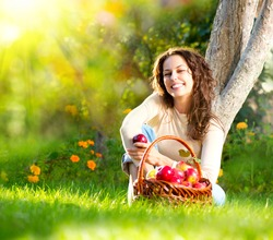 Happy Smiling Young Woman Eating Organic Apple in the Orchard.Basket of Apples. Harvest Concept.Garden