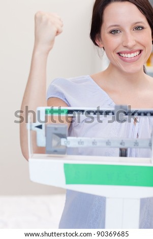 Happy smiling young woman on the scale