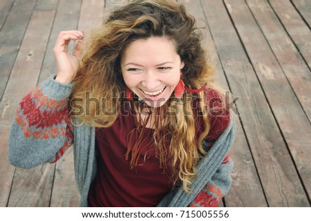 Happy smiling young woman outdoor portrait dressed in gray knitted jersey #715005556