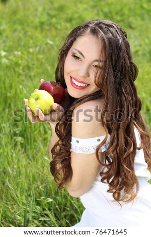Happy smiling young woman present apples on the nature