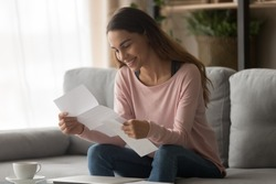 Happy smiling young woman student customer holding paper bank statement open read mail letter with good news, loan approval, receive scholarship admission money tax refund concept sit on sofa at home