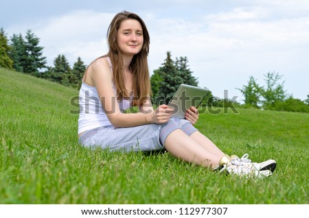 Happy smiling young woman using a touchpad tablet sitting outdoors in the sunshine on a green lawn