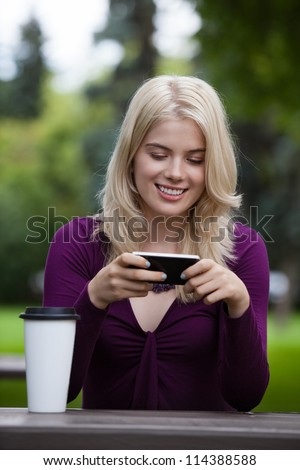 Happy smiling young woman using mobile phone in park