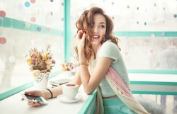 Happy smiling young woman using phone in a cafe. Beautiful girl in trendy spring colors.