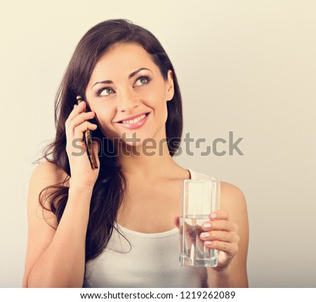 Happy smiling young woman with healthy skin talking on mobile phone and drinking clean water. Consulting the diet. Closeup portrait. Toned portrait