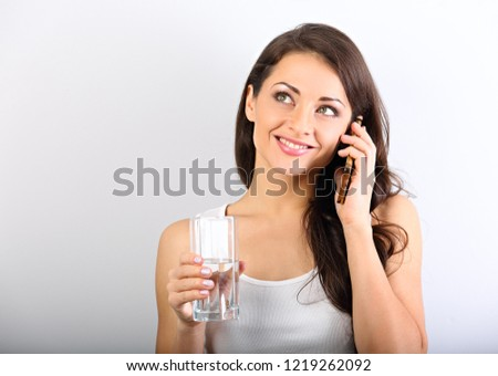 Happy smiling young woman with healthy skin talking on mobile phone and drinking clean water. Consulting the diet. Closeup portrait