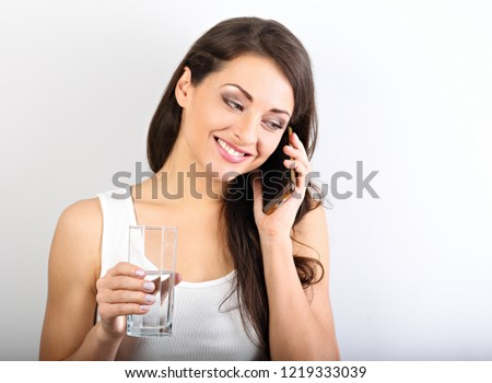 Happy smiling young woman with healthy skin talking on mobile phone and drinking clean water. Consulting the diet. Closeup portrait.