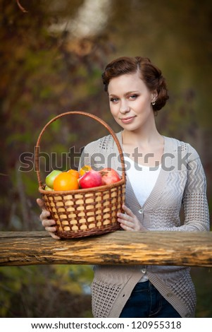 Happy Smiling Young Woman with Organic Apple in basket in the Orchard. Girl with Basket of Apples enjoying the nature. Harvest Concept. Garden. Provence romantic  brunette lady with hairstyle outdoors