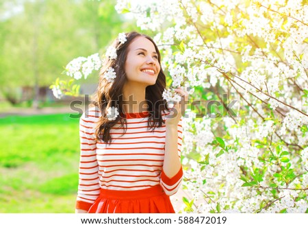 Happy smiling young woman with spring flowers at garden #588472019
