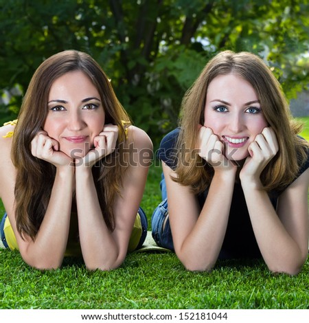 Happy smiling young women lying on grass against background of summer green park