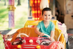 Happy smilling boy driving car toy at an amusement park. Toned photo.