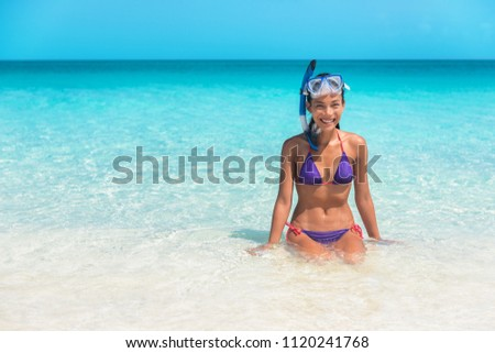 Happy snorkel girl having fun in ocean water snorkeling on Caribbean vacation in idyllic clean water beach. Watersport lifestyle.