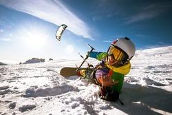 Happy snowboarder with kite lies in snowdrift. Sheregesh resort, Siberia, Russia
