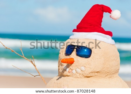 Happy snowman at the beach with sun glasses. His right arm is visible as well