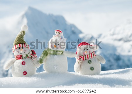 Happy snowmans in mountains (copy space)