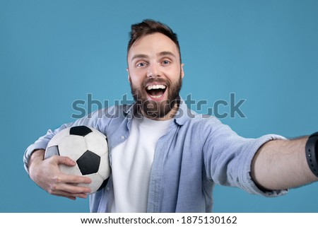 Happy soccer fan with ball taking selfie on mobile device over blue studio background. Positive football rooter making photo of himself after game, cheering for his favorite team Photo stock ©
