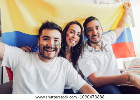 Happy soccer fans holding a colombian flag and looking at camera - Shutterstock ID 1090473686