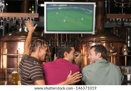 Happy Soccer Fans. Three Happy Soccer Fans Watching A Game At The Pub