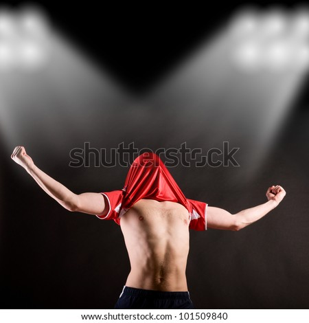 happy soccer player is celebrating in stadium light beams with jersey on head