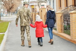 Happy soldier with family outdoors