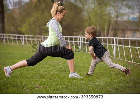 Happy son and mother are doing exercises in the summer park. on the stadium, outdoor. Sport activities with children. Healthy lifestyle. Fitness exercises. Young mother and son are stretching together