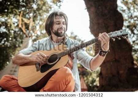 Happy song. Smiling bearded man singing songs playing guitar resting in nature #1201504312