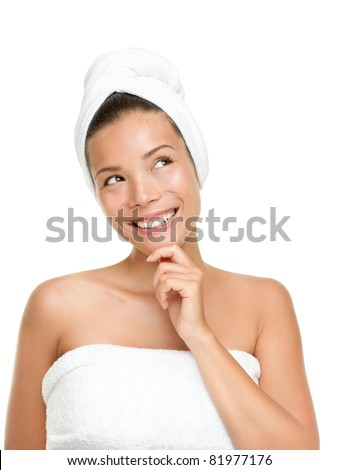 Happy spa woman thinking looking up isolated on white background. Beautiful smiling Asian Caucasian with towels.