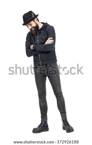 Happy spontaneous laughing hipster with fedora hat looking down. Full body length portrait isolated over white studio background.