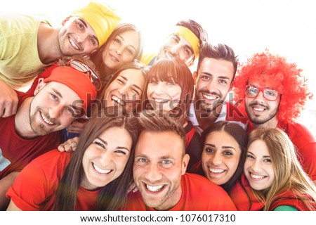 Happy sport friends taking selfie at world soccer event - Friendship concept with young people having fun at international stadium - Football cup championship concept on warm sunsine halo filter