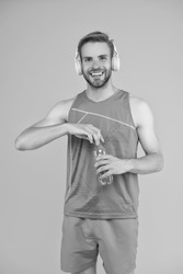 Happy sportsman hold water bottle. Fitness trainer. Feeling thirst. Thirst and dehydration. Thirst control. Drinking water. Cheerful athletic guy listening music. Keep body and mind in good shape