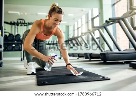 Happy sportswoman cleaning exercise mat with disinfectant after sports training in health club.  Foto stock ©