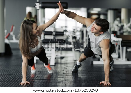 Happy sporty couple giving high five to each other while doing push up together in gym. Unity and support, copy space