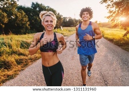 Happy sporty couple preparing for marathon in the nature. Sunny summer day.