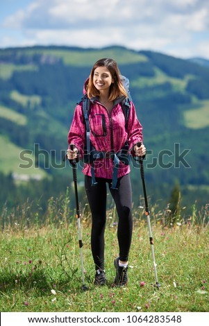 Happy sporty woman tourist with backpack and trekking sticks, wearing sports wear, standing on the top of a hill, smiling, looking away, resting after hiking, enjoying summer day in the mountains #1064283548