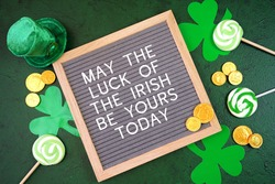 Happy St Patrick's Day felt letterboard message board styled with leprechaun hat, shamrocks, and chocolate gold coins, on a textured green background. May the Luck of the Irish greeting.