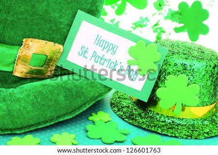 Happy St Patrick's Day tag with party hats and shamrocks over white