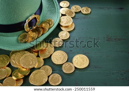 Happy St Patricks Day leprechaun hat with gold chocolate coins on vintage style green wood background with copy space. .