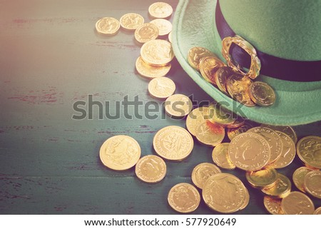 Happy St Patricks Day leprechaun hat with gold chocolate coins on vintage style green wood background,, with applied retro style faded filters.