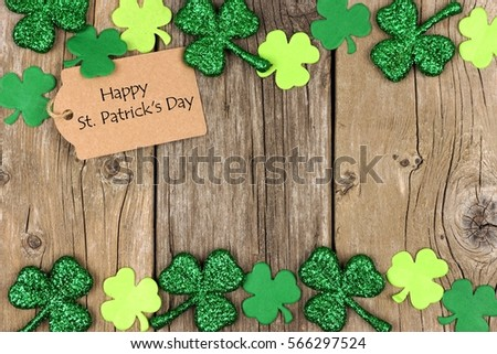 Happy St Patricks Day tag with double border of shiny shamrocks over a rustic wood background