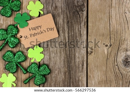 Happy St Patricks Day tag with side border of shiny shamrocks over a rustic wood background