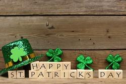 Happy St Patricks Day wooden blocks with shiny shamrocks and leprechaun hat on a wooden background