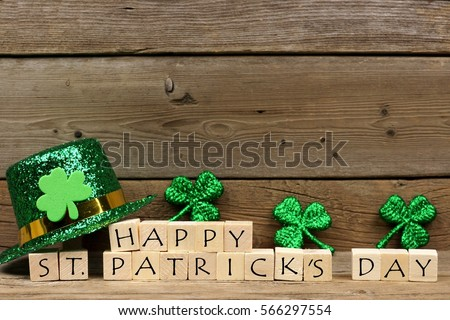Happy St Patricks Day wooden blocks with shiny shamrocks and leprechaun hat on a wooden background
