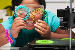 Happy STEM student smiles and shows off the colorful 3d printed shapes, plastic parts on the print bed with skirt for plate adhesion.