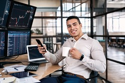Happy stock broker resting in office, using modern smartphone, drinking beverage and sitting near monitor with cryptocurrency information data on finance market graph