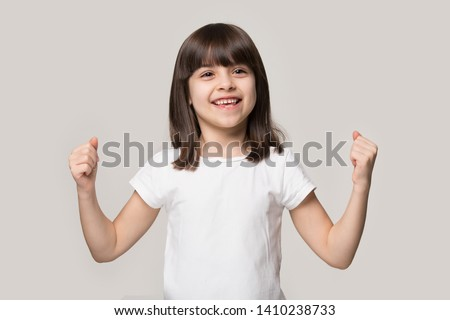 Happy strong little girl showing hands bicep strength make fists feels healthy posing isolated on grey studio background, active preschool child, physical health, well-being develop potential concept